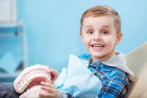 happy blonde boy in a dental chair holding a giant model of a jaw with teeth