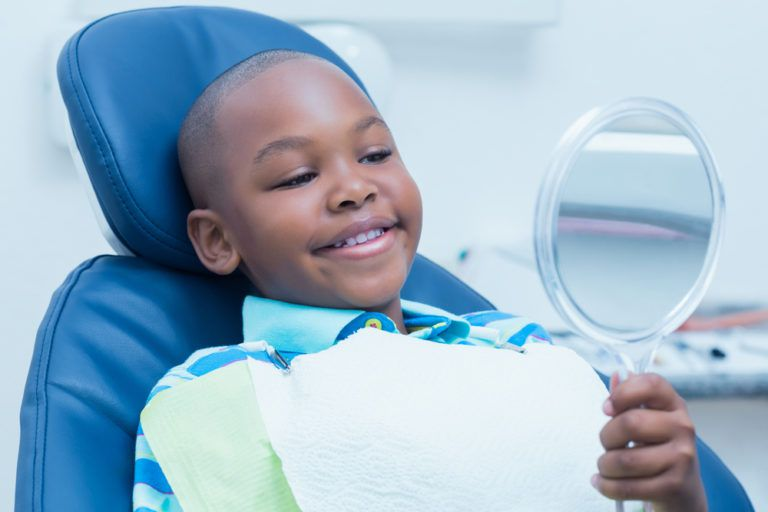 young child smiling at himself in the mirror at dental visit