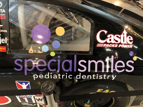 closeup side of vehicle with logo of dental on black car
