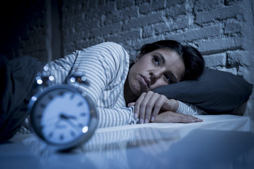 Woman lying in bed awake in the middle of the night
