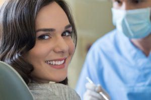 A smiling woman at the dentist looking back at the camera over her shoulder
