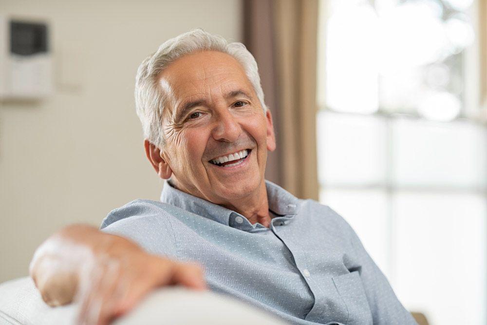 smiling man staring at camera blue shirt