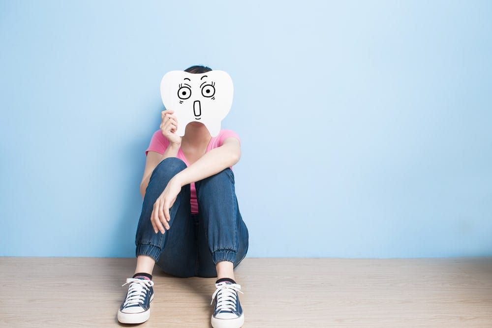 Woman holding a paper cut out of a giant scared tooth in front of her face while sitting against a light blue background