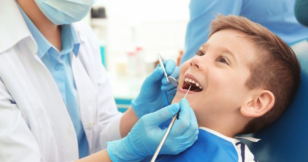 Dentist examining little boy's teeth