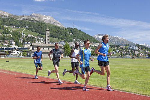 5 men running on a track