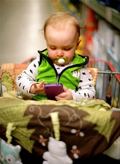 toddler in shopping cart playing on a cell phone