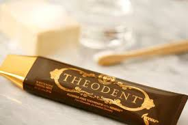 Theodant chocolate toothpaste next to toothbrush on counter