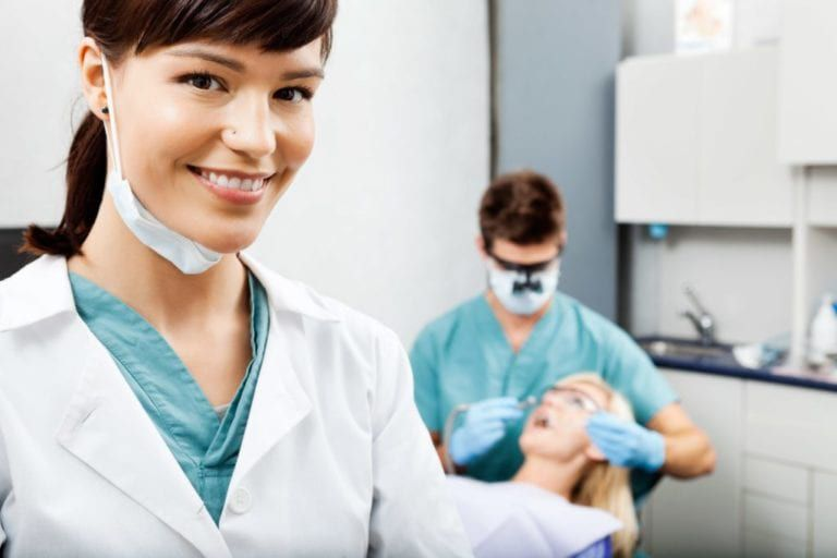 female dentist smiling with a male dentist cleaning a female patient teeth in the backfground