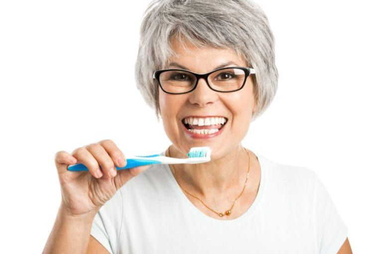 woman showing her teeth while holding a toothbrush