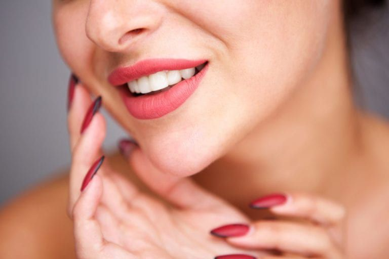 woman smiling with her hands framing her jaw