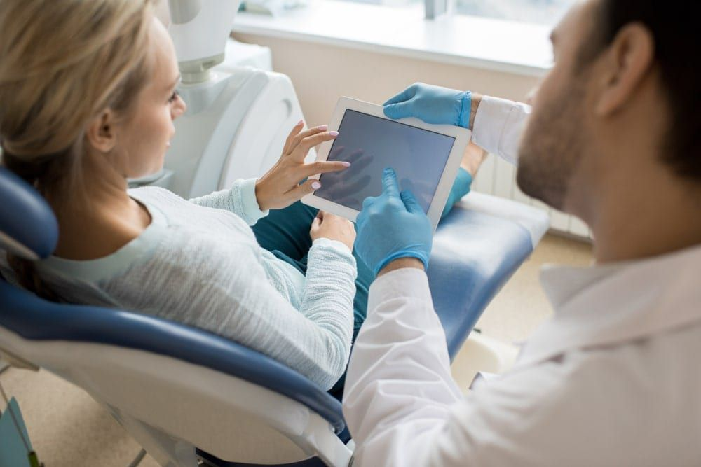 Dentist explaining treatment plan using a tablet