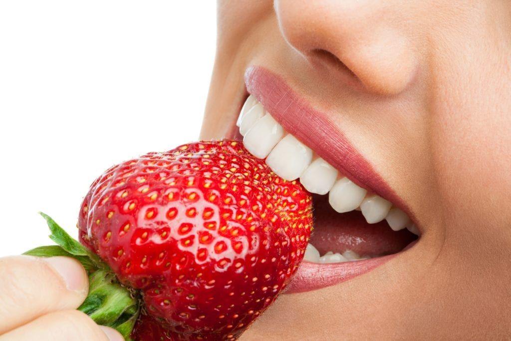 closeup of a woman biting into a strawberry