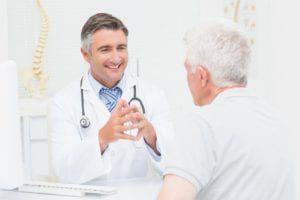 doctor talking to elderly patient smiling