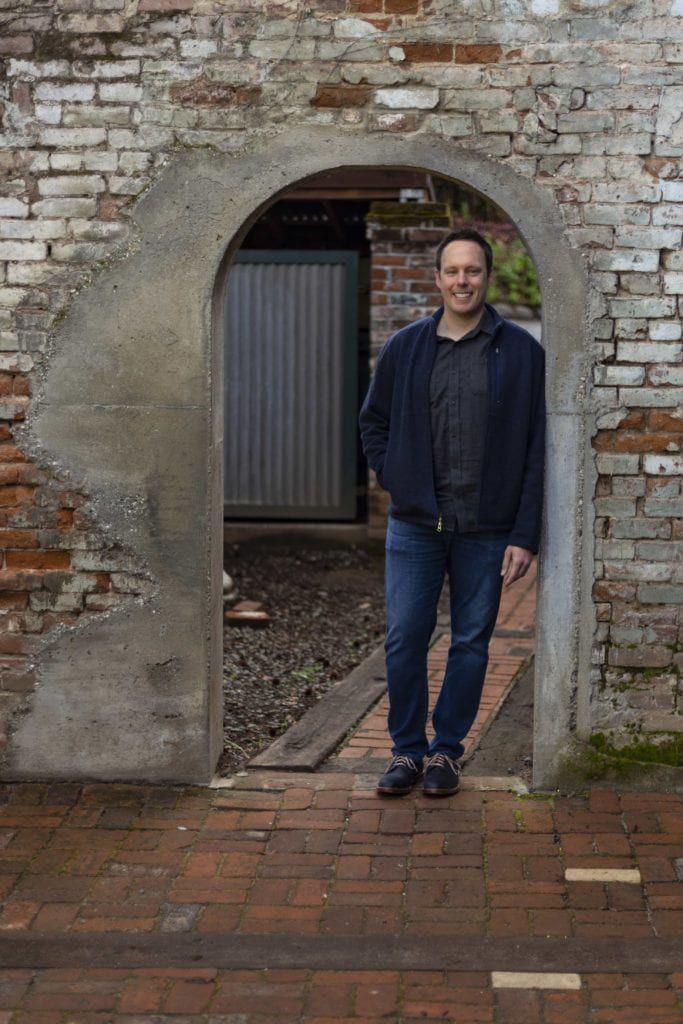 doctor posing behind brick doorway