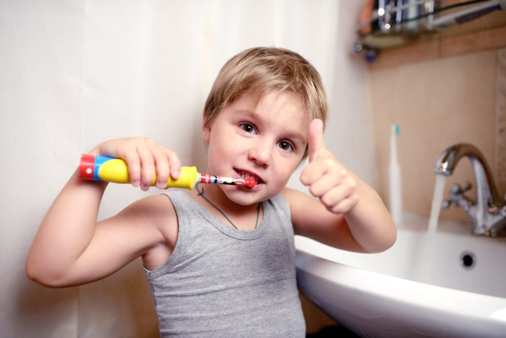 Young boy brushing his teeth and making a thumbs up