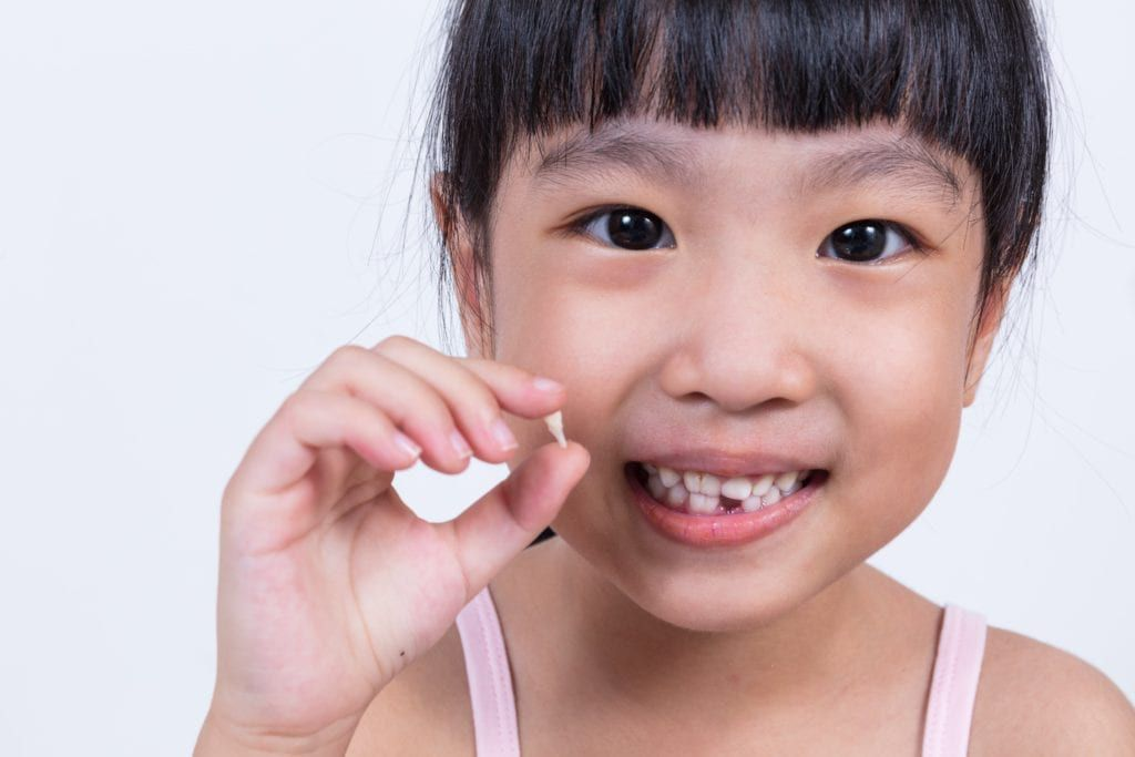 young girl holding her missing tooth