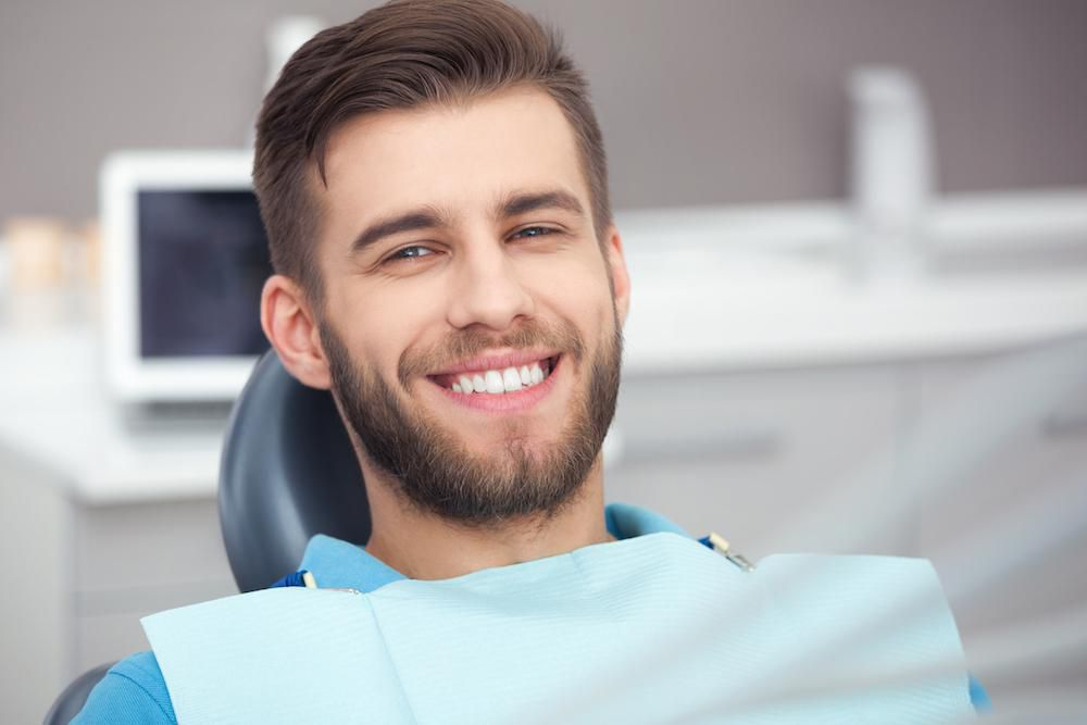 young man smiling at dental office
