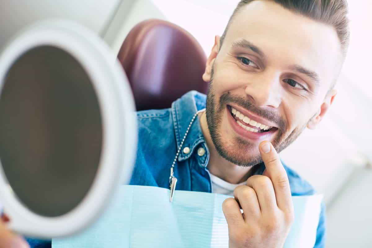 man in dentist chair checking his teeth in a mirror