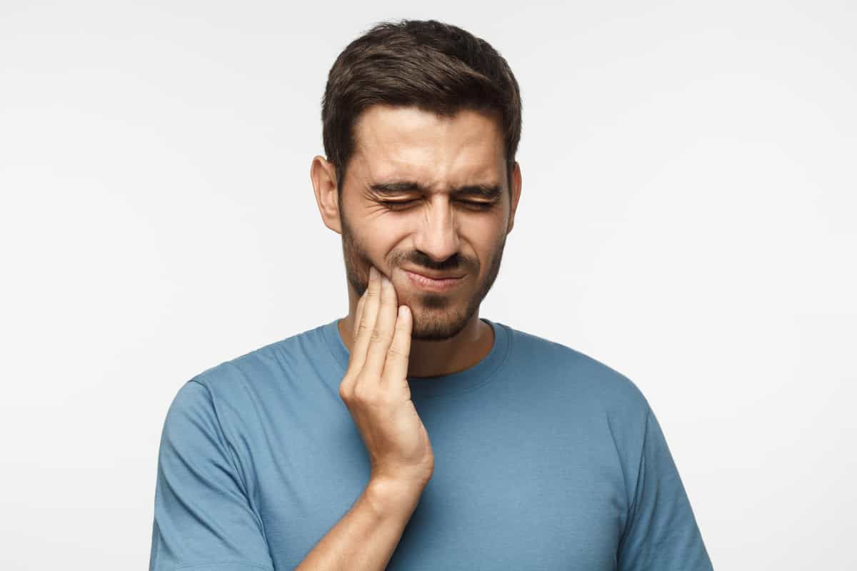 man holding his cheek in pain