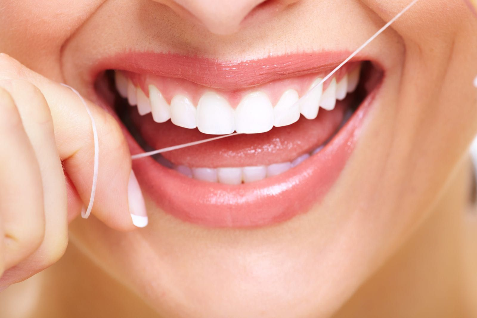 Woman with straight teeth flossing
