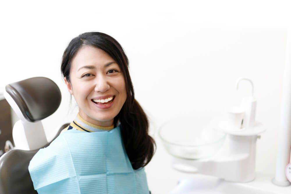 smiling patient sitting in dental chair, waiting on surgery