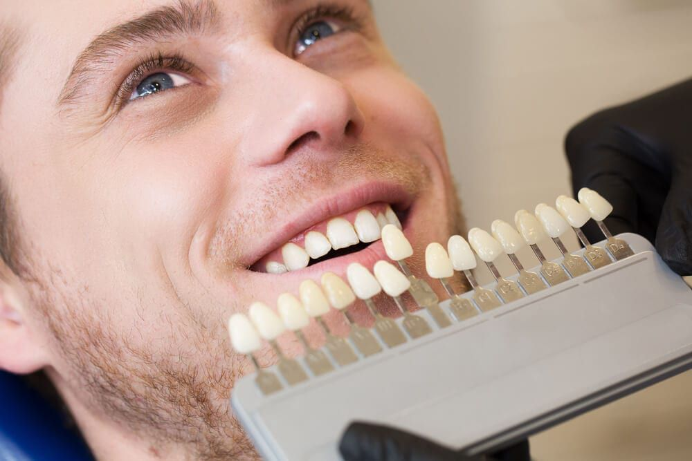 male dental patient smiling with dentist, matching veneer shades