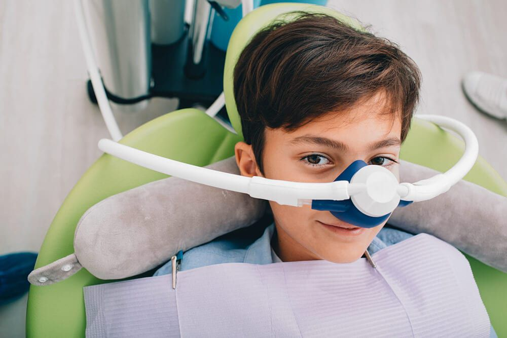 child waiting for dental work with sedative mask